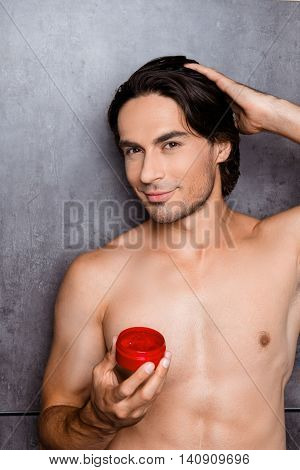 Muscular Man Holding Jar Of Gel For Hair And Making Hairstyle