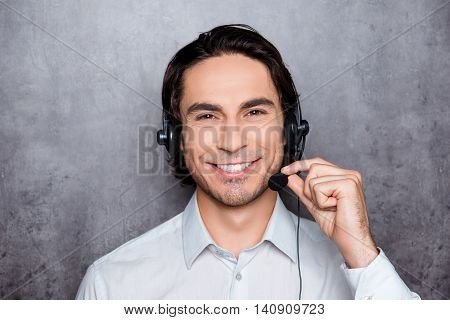 Portrait Of Handsome Young Operator In Work In Call-centre With Headphones And Smiling