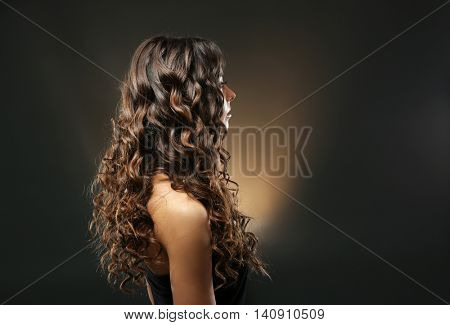 Young beautiful woman with nice hairdo on dark background