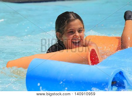 Rhodes Greece-July 30 2016:The young girl in the pool after mat racer slide in Water park .Mat racer slide is very popular popular game for adults and children in park.Water Water Park is located on the island of Rhodes in Greece and one of the most popul