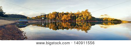 High resolution panorama. Lake with reflection of forest in water, mirror-like surface. Yellow autumn leaves on trees, fog.
