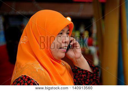 Singapore - December 17 2007: Muslim woman wearing a bright orange head scarf talks on her cell phone walking along Serangoon Road in Little India