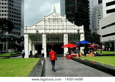 Singapore - December 12 2007: MRT subway entrance kiosk at Raffles Place surrounded by corporate towers and banks