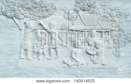 Stone carving of Traditional Thai culture on temple wall
