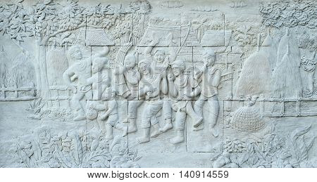 Stone carving of traditional Thai musical instrument on temple wall