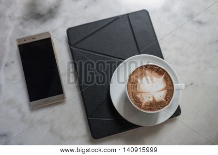hot fresh coffee in white cup on marble table on tablet and mibile phoe and white saucer cappuccino coffee mocha coffee espresso coffee latte coffee