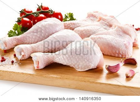 Raw chicken wings and drumsticks on cutting board on white background