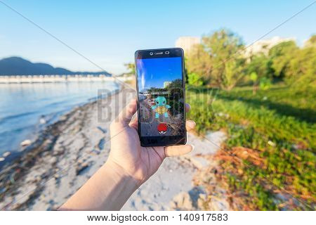 California, United States - July 30, 2016: Close up of a man holding a unbranded smartphone while playing Pokemon Go game with blur beach background