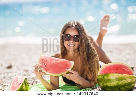 A beautiful young woman of Caucasian appearance with long straight blond hair and gray-green eyes,laying on a beach towel on the green against the blue of the ocean wearing a black bikini,holding a slice of ripe watermelon with your legs crossed