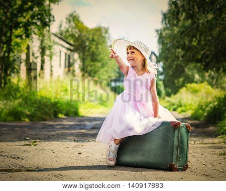 Little girl sitting on suitcase and pointing up with a finger.