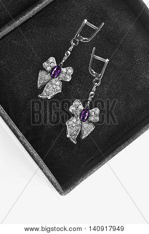 Amethyst earrings in the shape of bows in black jewel box closeup