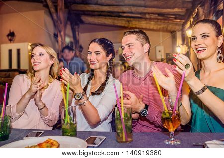 Young beautiful people with cocktails in bar or club having fun, enjoying show, clapping