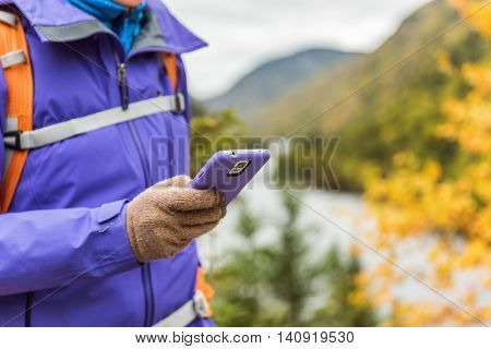 Person hiking in nature using smartphone app with touch screen tech gloves during hike in autumn travel adventure in mountain forest outdoors. Beautiful landscape background.