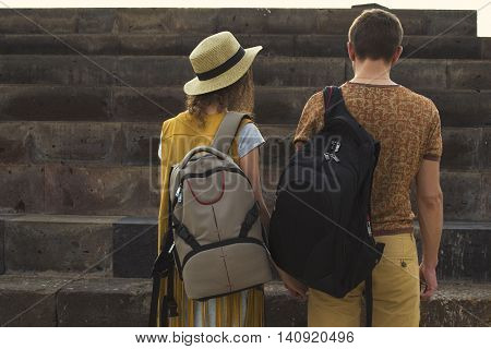 Photo of the Concept traveling together honeymoon wanderlust. Stylish couple in love with backpacks on shoulders. Back view.