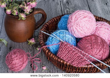Tangles of wool yarn and a fragment of knitting in a wicker basket, near earthenware mug with dried flowers.