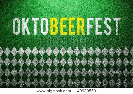 Oktoberfest sign with white and green rhombus pattern on artificial turf. Studio shot. Green background.