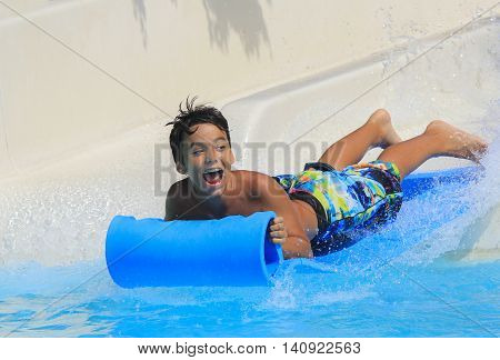 Rhodes Greece-July 31 2016:The boy joying on the mat racer slide.Mat racer slide is very popular for young people in the Water Park. Water Park is located on the island of Rhodes in Greece and one of the most largest in Europe and is a very popular place