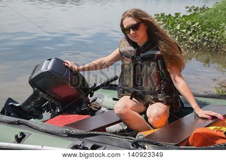 girl in a life jacket sits in a boat with outboard motor