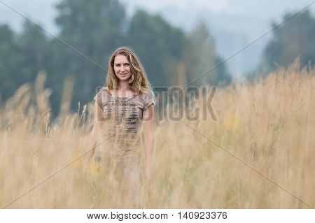 The girl in the field among high yellow grass