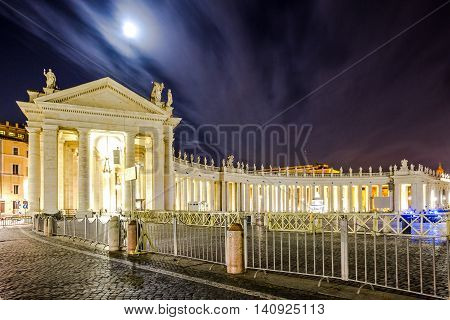 The colonnade of St. Peter's Square in Vatican City in Rome illuminated at night.