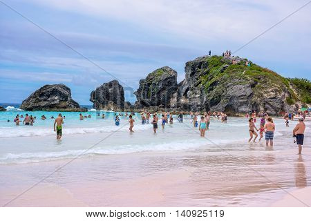 HORSESHOE BAY BERMUDA - MAY 26 - Crowds of swimmers in the surf with large rock formations of Horseshoe Bay on May 26 2016 in Bermuda.