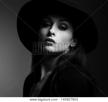 Elegant makeup woman in fashon hat posing on dark shadow background. Black and white portrait. Closeup