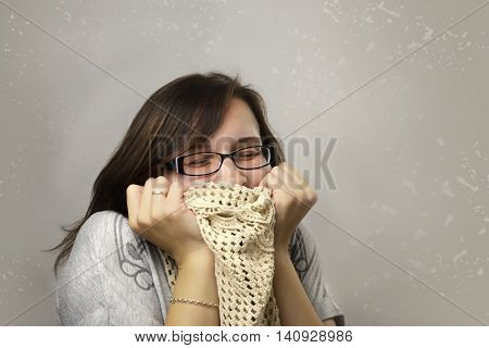 Woman loves clothes. Happy woman in glasses adores knitted scarf. Person enjoys shopping and hugs the purchases. Woman got a discount on sale and bought favorite clothe. Shopper with clean background