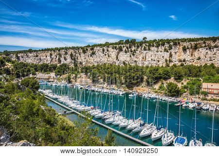 White sailboats moored in rows near the shore. Picturesque small bay - Calanques between Marseille and Cassis
