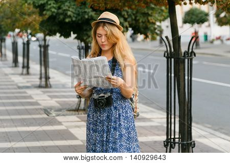 Portrait of a young blonde woman traveler with a backpack on her shoulders in a hat got lost in a foreign city and trying to orient yourself on the map.