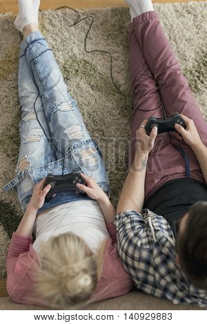 Top view of couple in love enjoying their free time sitting on the carpet on the floor next to the couch playing video games and having fun. Focus on the man's hands