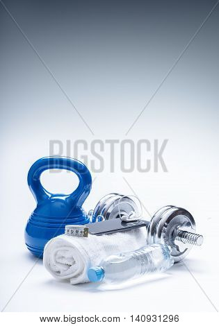Fitness Equipment. Kettlebell towel dumbbells water smart phone with headphones and measuring tape.