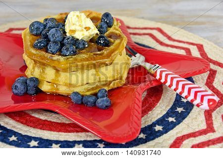 Waffles stack with blueberries and fork on red star plate.