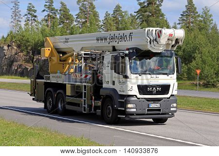PAIMIO, FINLAND - JULY 1, 2016: White MAN TGS 26.400 boom truck moves along motorway in South of Finland on a sunny day of summer.