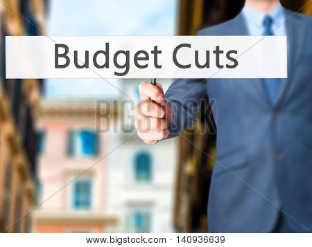 Budget Cuts - Businessman Hand Holding Sign