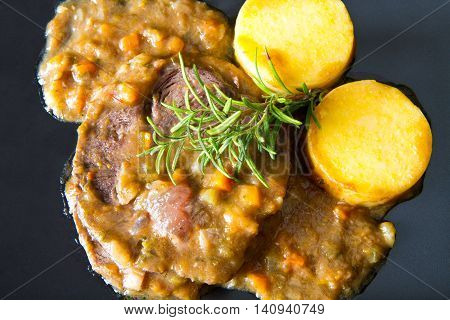 a dish with braised meat with polenta