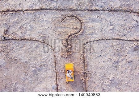 tipper with stones at crossroads. toy yellow truck on the sand at the fork in the road. drawn a question mark. the concept of honest business. top view
