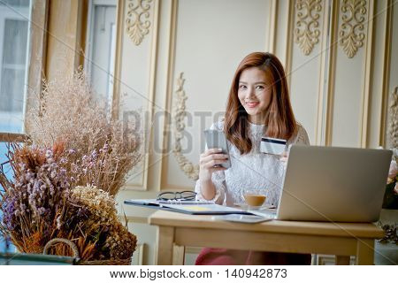 Happy woman shopping online holding credit card using laptop computer electronic purchase.