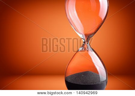 Close up hourglass on a orange background