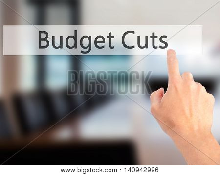Budget Cuts - Hand Pressing A Button On Blurred Background Concept On Visual Screen.
