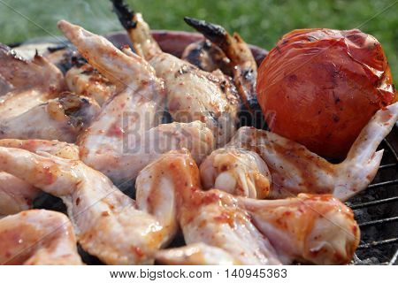 Chicken Wings And Tomato On The Grill