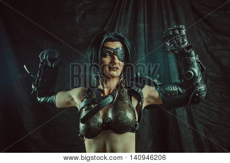 Powerful one-eyed steam punk woman in metal lingerie is showing us her iron muscles.