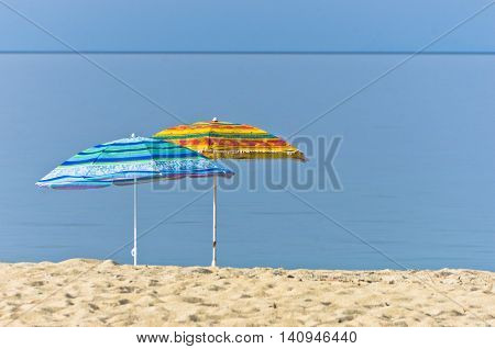 Yellow and blue sunshades on sandy beach against blue sky in Sithonia, Greece