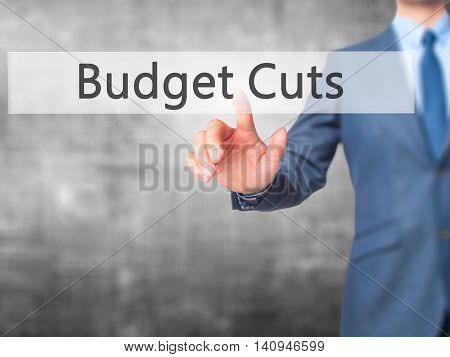 Budget Cuts - Businessman Hand Touch  Button On Virtual  Screen Interface