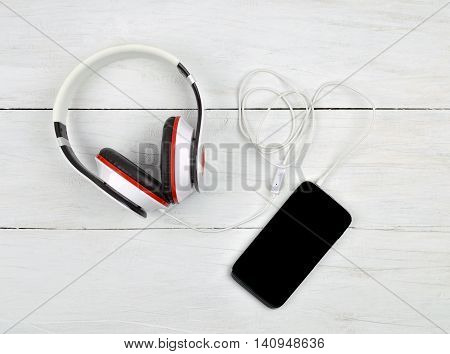 Small stylish little things - today's youth the attributes. Listen to music. Smartphone and headphones on a wooden background. Relaxation. Top view.