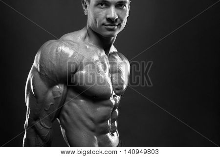 Strong bodybuilder with six pack. Athlete man with perfect abs, shoulders, biceps, triceps and chest, personal fitness trainer flexing his muscles