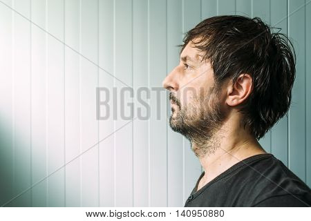 Adult unshaven casual male profile portrait with copy space man looking toward sunlight that is coming from the window