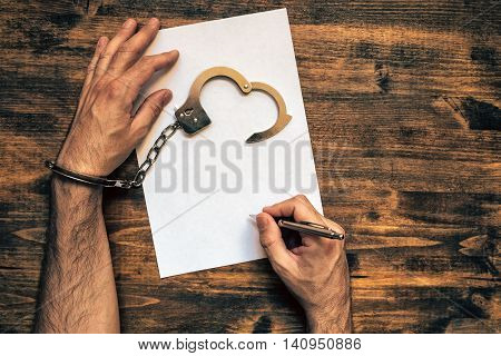 Male hands cuffed signing confession top view of police investigator detective desk