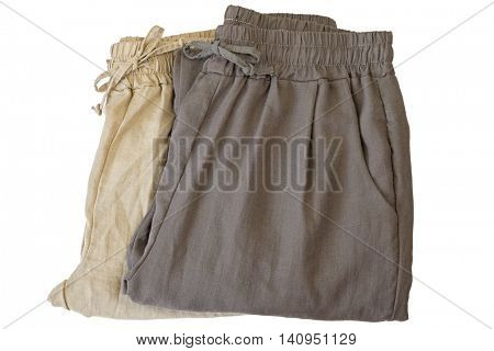 Pants made of cotton. Folded trousers in light dark brown, natural fabric cloths isolated on white background