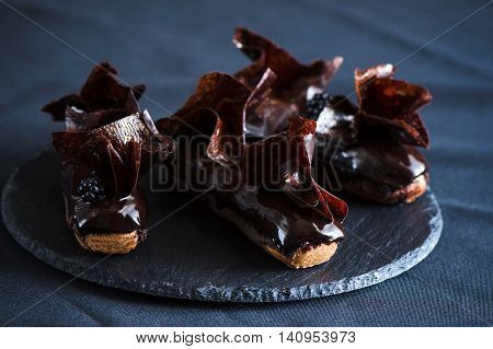 Chocolate choux pastry, chocolate crumble, creme caramel with black chocolate, chantilly with beans thin, extra-black glaze and crunchy chocolate flakes