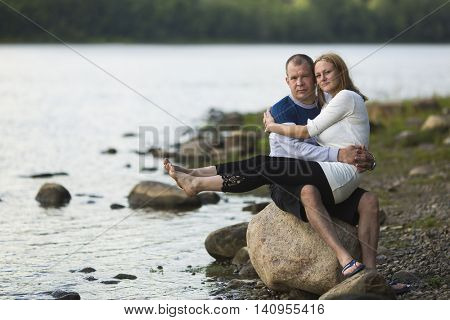 Young couple sitting on a rock by the river. Honeymoon.